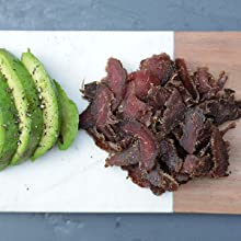 grass fed biltong jerky served with healthy fats from an avocado, on a plate.