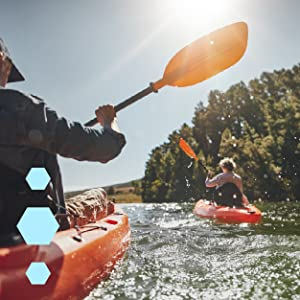 Picture of a man and woman kayaking in beautiful green water on a bright sunny day.