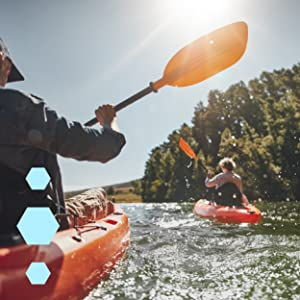 Two people in orange kayaks paddling down a river on a sunny day, trees in the background