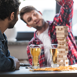 men playing game with upside down beer cups on table