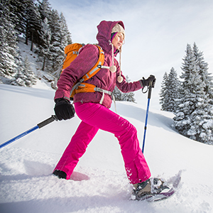 Girl snow shoeing with ski poles in the snow with backpack and smile