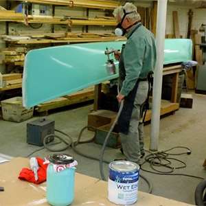 Man in workshop wearing mask and spraying TotalBoat Wet Edge Sea Foam Topside Paint on his canoe