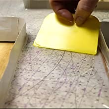 Using an epoxy spreader to distribute TotalBoat clear TableTop Epoxy evenly across the table surface