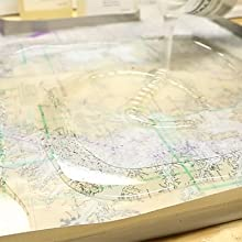 Pouring mixed TotalBoat clear TableTop Epoxy onto a prepared chart table surface.