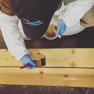 Applying TotalBoat Gleam 2.0 marine spar varnish using a natural bristle brush.
