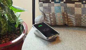 QiStone+ charging a phone on a sofa.