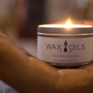 a lit sandalwood candle in hand palm