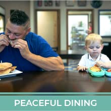 """A small child and adult man eating at a table. Text reads """"Peaceful Dining."""""""