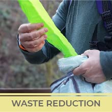 """A hand pulls a green diaper baggy out of a small pouch. Text reads """"Waste Reduction."""""""