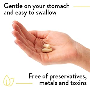 Woman hand holding 2 Prenatal pills gentle on your stomach, free of preservatives, metals and toxins