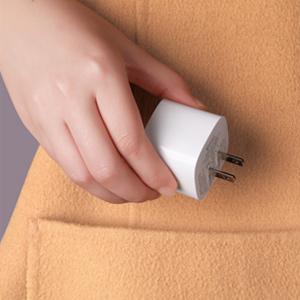 A hand hold the wall charger. The Charger is small so that it can be put into pocket easily
