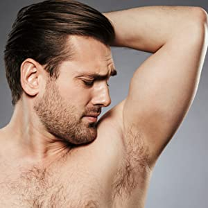 Close up of handsome shirtless man smells his armpit
