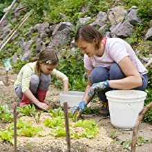 mother and daughter transplanting seedling outdoors in garden