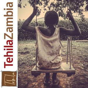 African child with his back to camera, sitting on swing.