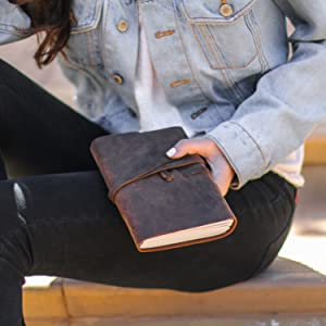 Girl holding the leather notebook so that you can see you can take it with you wherever you go