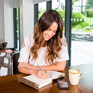 Woman in cafe writing in leather journal with coffee cup