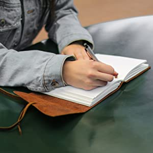 Leather Bound Journal being written in with a pen on the unlined white cotton paper pages
