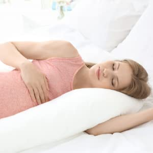 Pregnant woman in pajamas using pillow for head and neck support