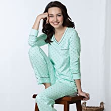 close up of model wearing the mint green and gray polka dot cotton pjs seated on a stool