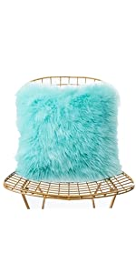a light green faux fur pillow on the chair