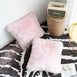 2 pink faux fur pillows on the floor