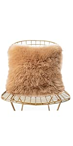 a light khaki faux fur pillow on the chair