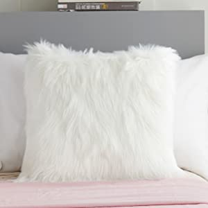 a white faux fur pillow in the bed