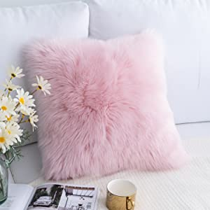 a pink faux fur pillow cover on the sofa