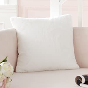 a white faux fur pillow in the sofa