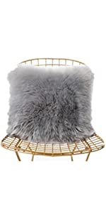 a grey faux fur pillow on the chair