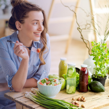 Healthy young woman enjoying a salad for lunch. Zhou Black Seed Oil can help curb your appetite.