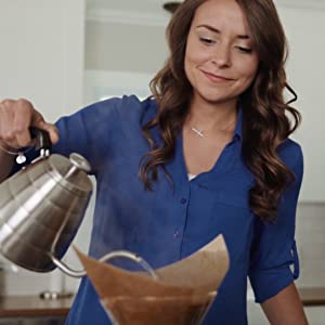 Woman in blue shirt pouring hot water out of gooseneck kettle over Chemex Coffeemaker in kitchen