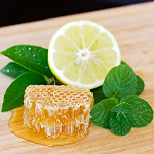 A square of tasty organic raw honey comb by a lemon garnished with mint all sitting on a wood table