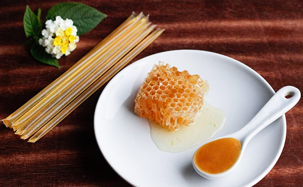Square of honey comb and spoon of honey on a white plate next to honey sticks