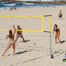 Fit and healthy beachgoers playing beach volleyball