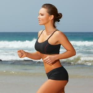 Healthy slim lady running on beach