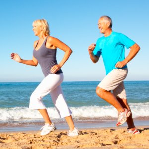 Middle aged healthy couple running on beach
