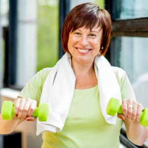 Lady concentrating on lifting light weights during training