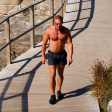 Fit energetic man walking on beach track