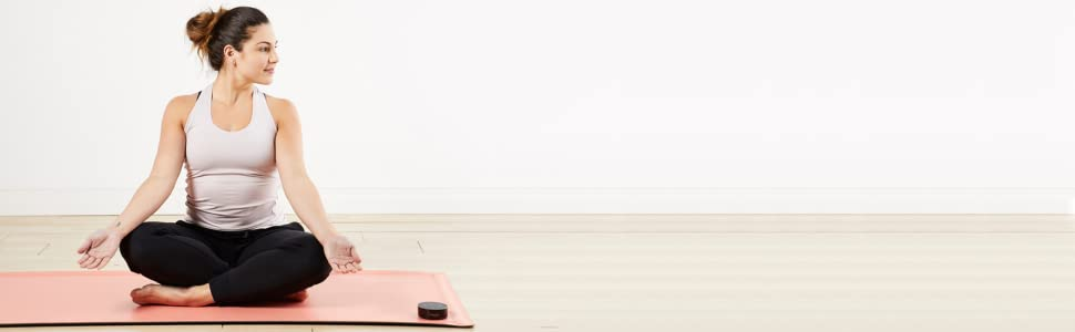 girl sitting in front of wall with yoga mat and alexa