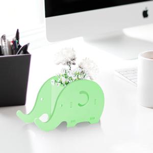 green elephant holder on the desk
