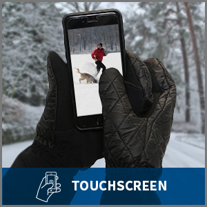 Hands in black mittens holding a phone displaying winter scene. The mittens are touchscreen.