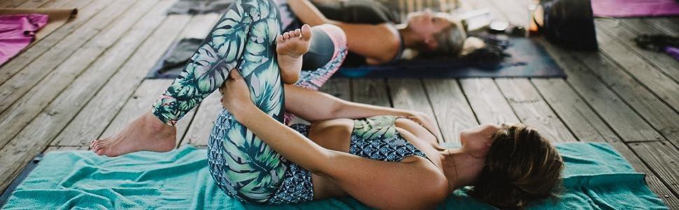 Yoginis reclining on yoga towels.