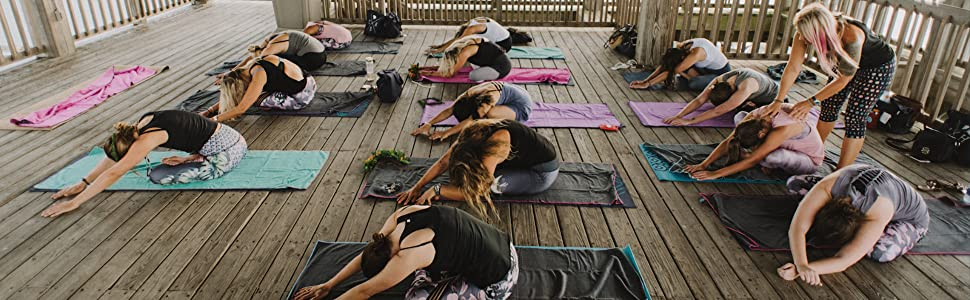 Multiple yogis in a seated forward bend.  One yogi is being adjusted by a teacher.