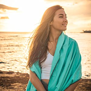 Girl sitting on the beach with a towel draped over shoulders.