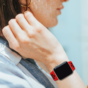 A girl wear the white clothes and a red black apple watch band.