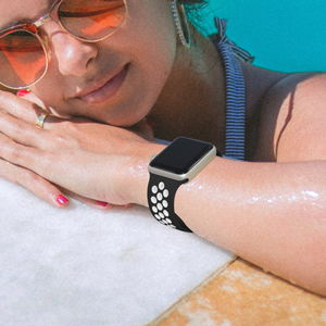A woman leaning beside the pool and wear the black white apple watch band and sunglasses.