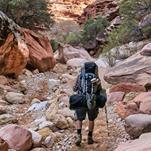 Man hiking with with stainless steel mugs attached to his backpack outdoors during camping trip