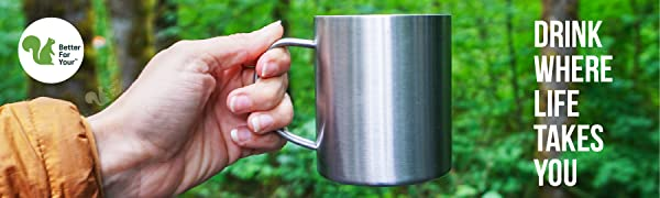 Camper holding stainless steel coffee mug in forrest during camping RV roadtrip
