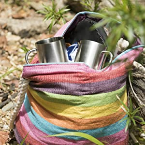 Two stainless steel mugs in a colorful bag outdoors on camping trip
